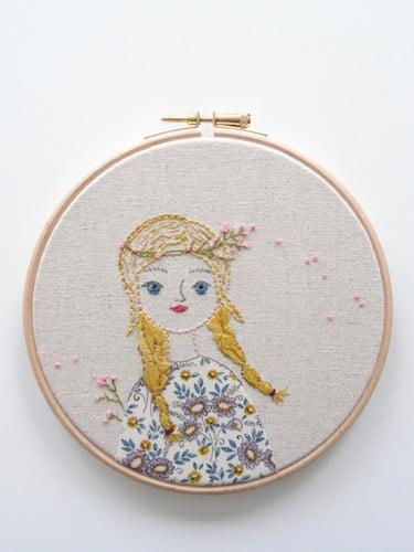 geborduurd portret van meisje met blonde vlechten